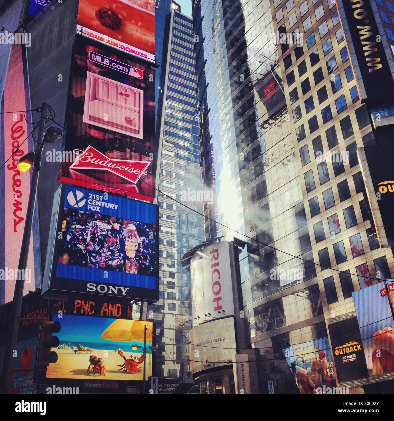 Réflexions du soleil et annonces à Times Square New York City Banque D'Images