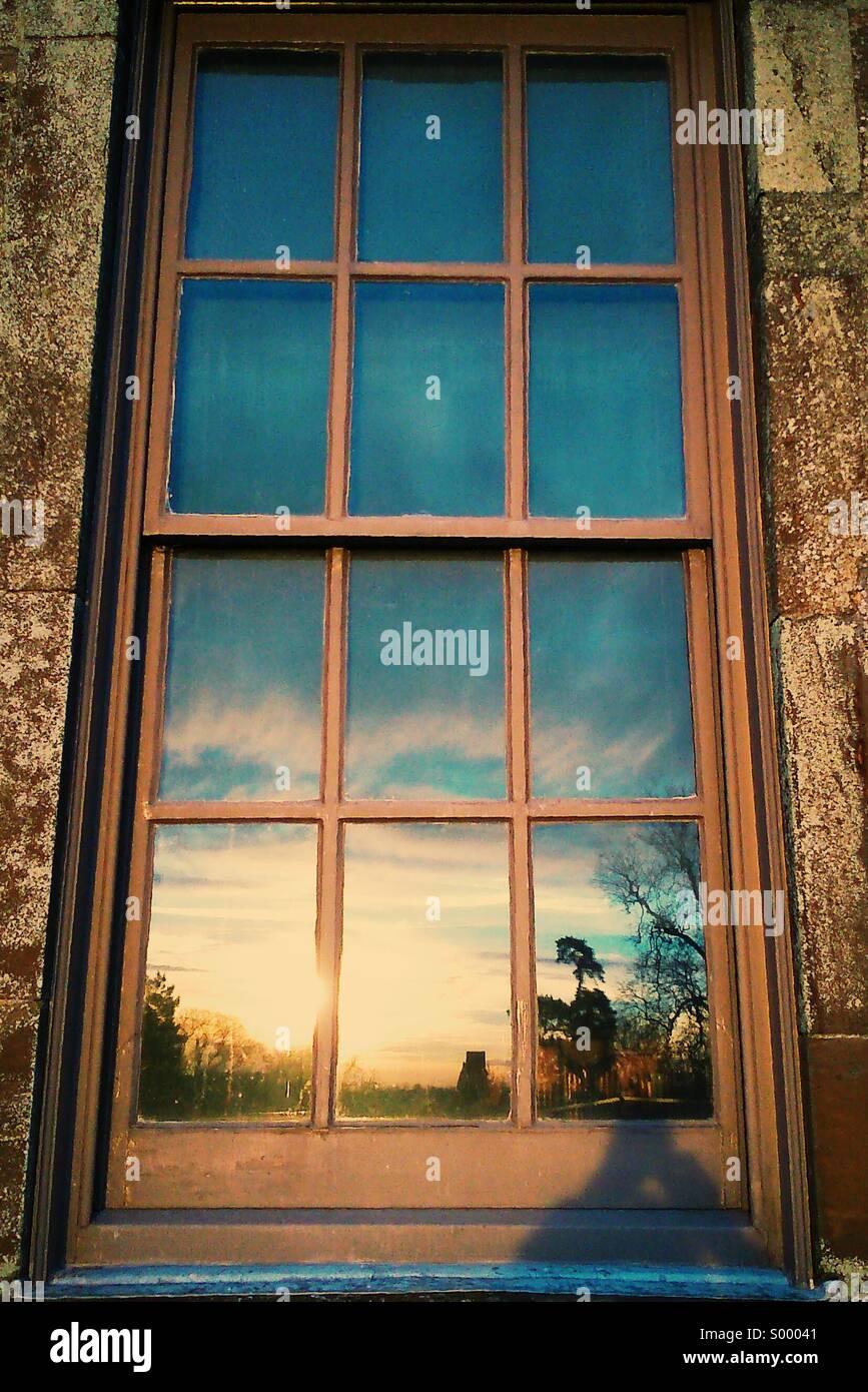 Coucher du soleil reflétée dans la fenêtre Photo Stock