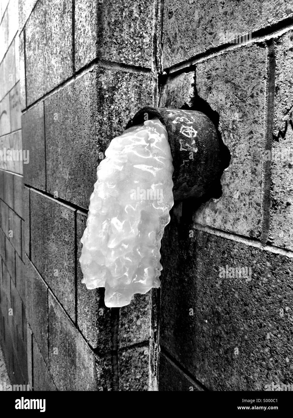 Ice se déverse d'un tuyau sous le pont de Manhattan à Brooklyn, New York lors d'une froide journée Photo Stock