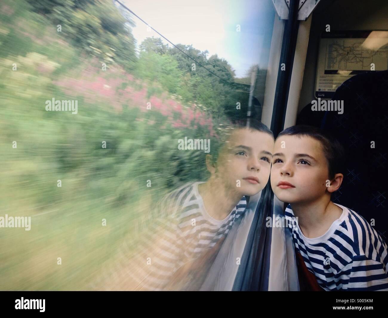 Jeune garçon contempler de la fenêtre du train Photo Stock