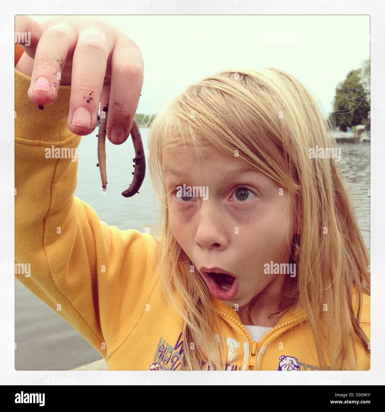 Une fille s'illuminera en regardant un crawly intimidées usés. Photo Stock