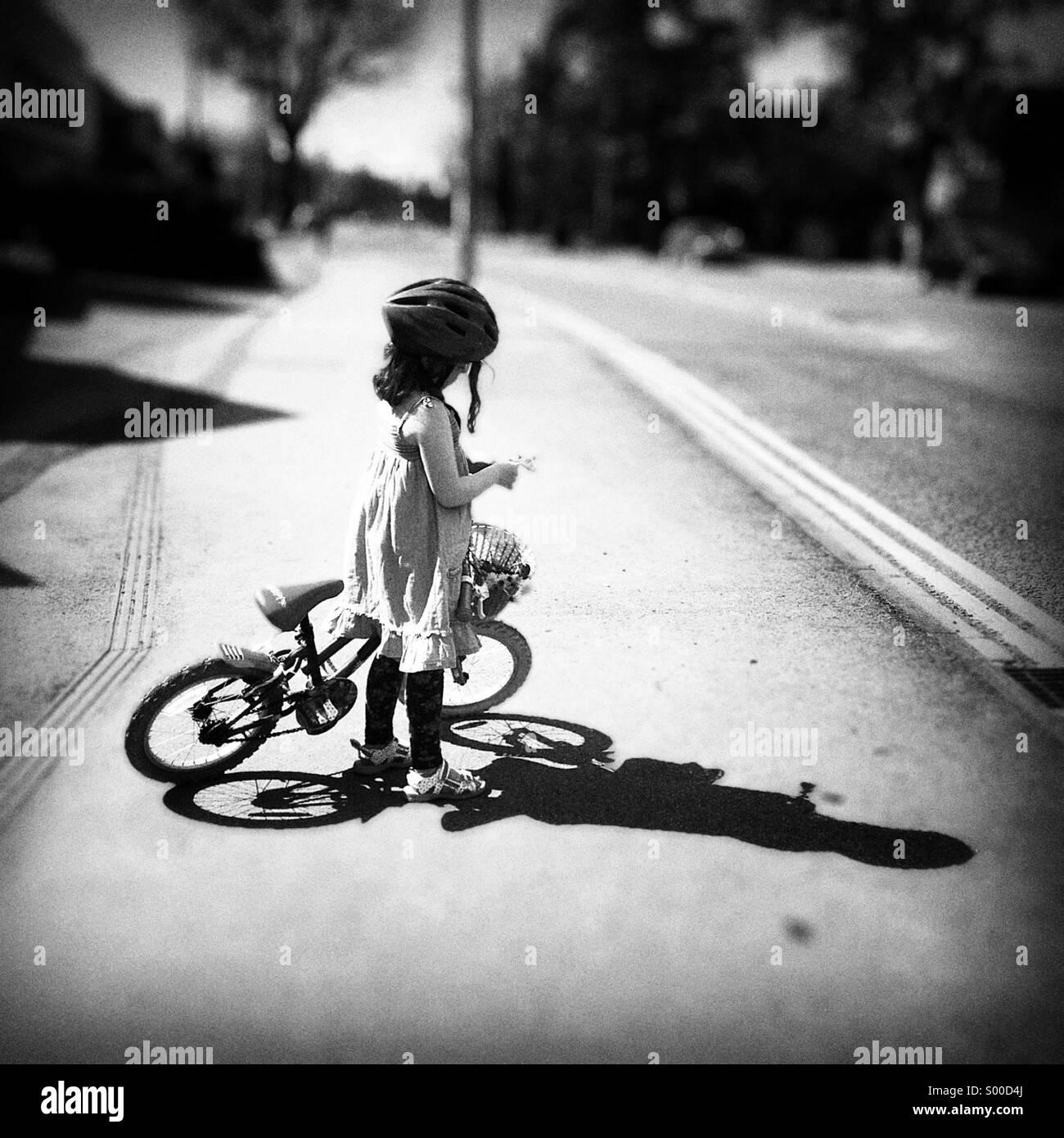 Jeune fille avec son vélo et un panier de fleurs. Ombre et soleil fort Photo Stock