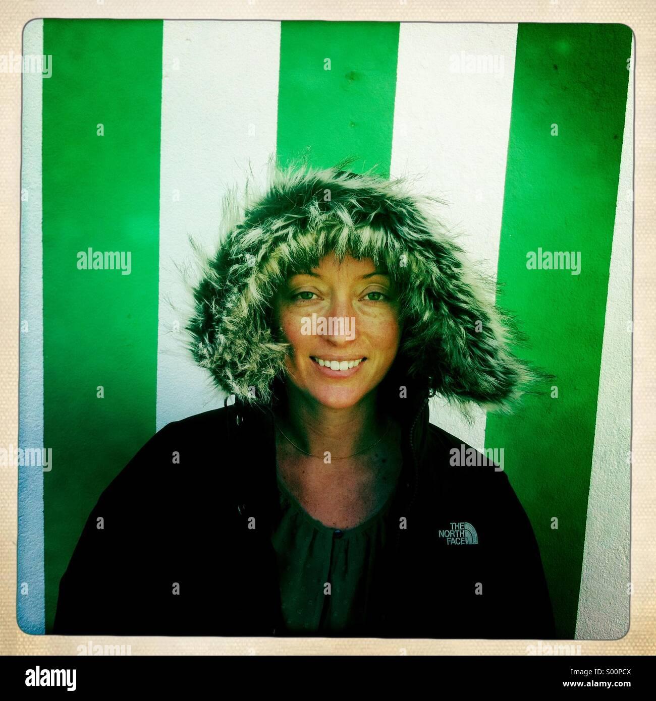 Une jeune femme se tient debout devant un mur blanc et vert. L'Irlande. Banque D'Images