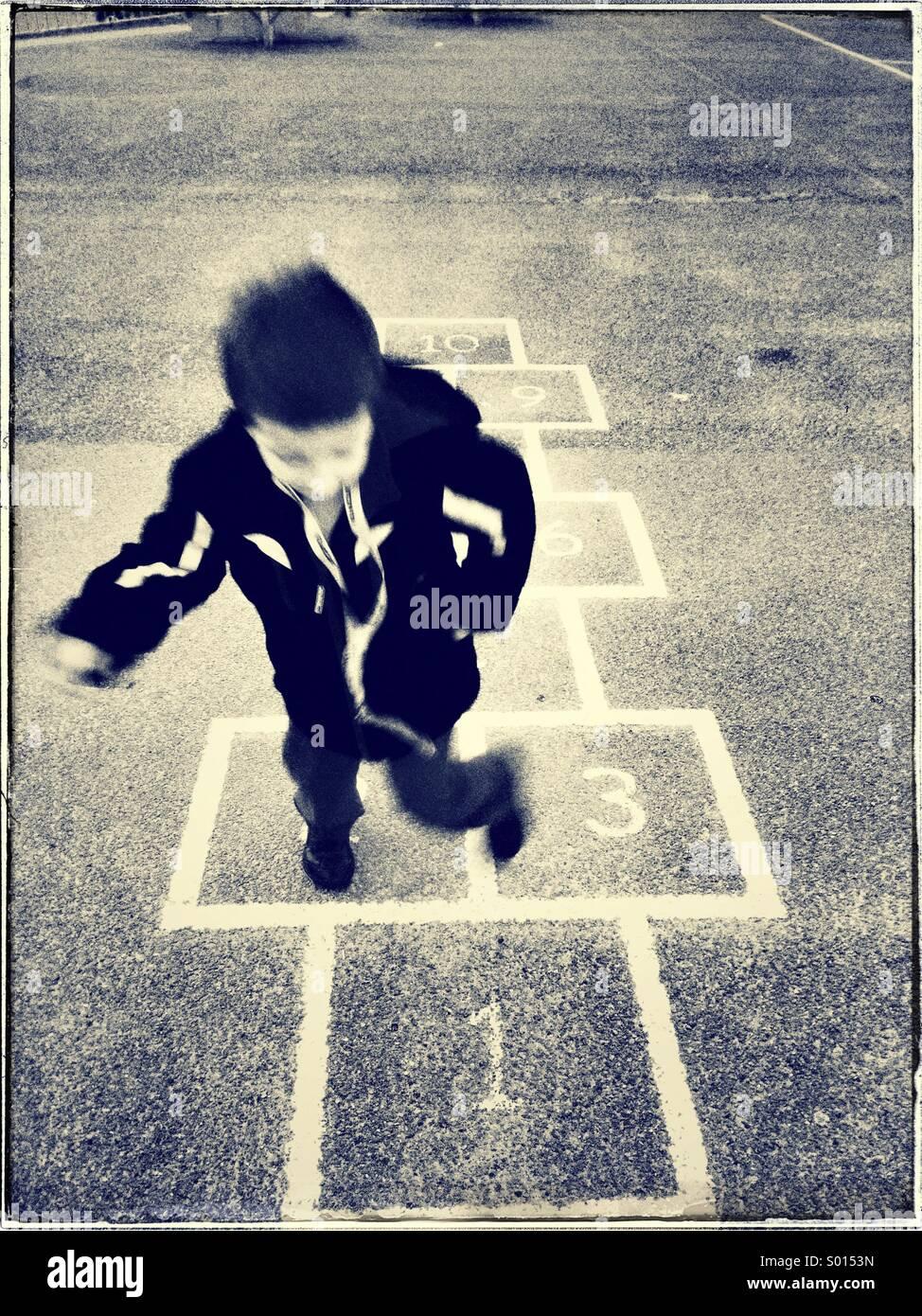 Enfant jouant à la marelle Photo Stock