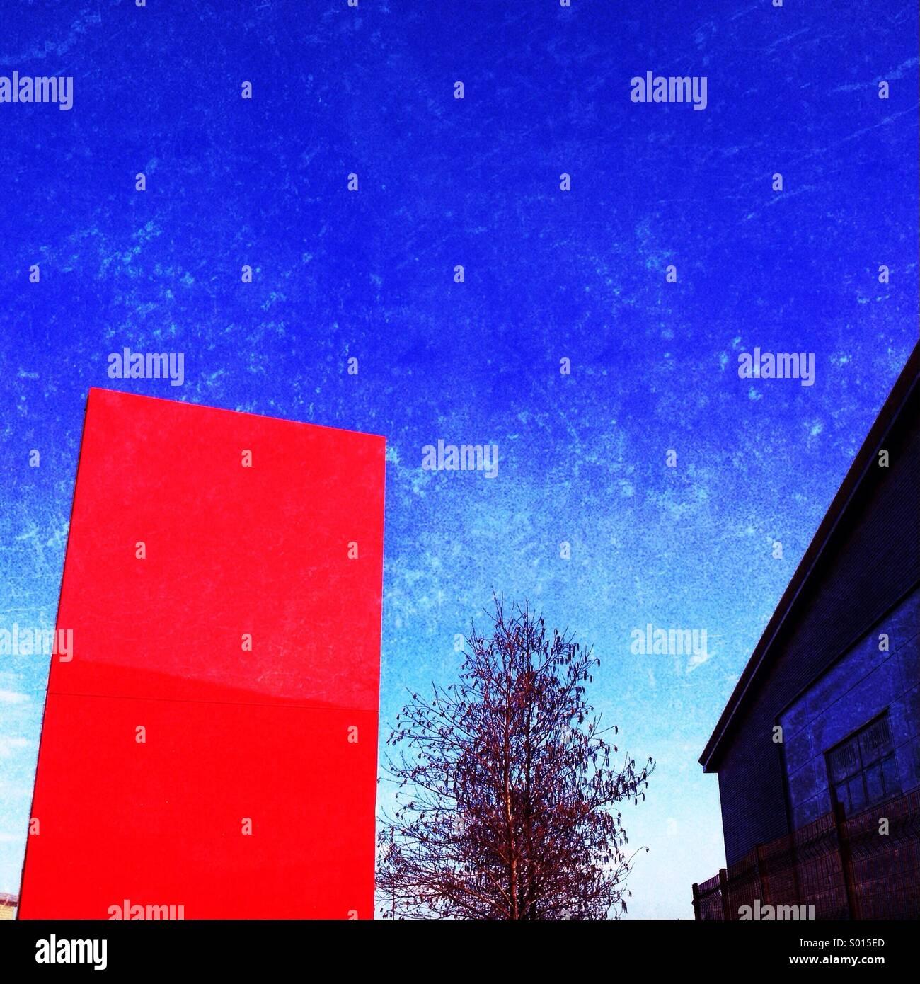 Panneau rouge, l'arbre et de l'unité industrielle contre le ciel bleu Photo Stock