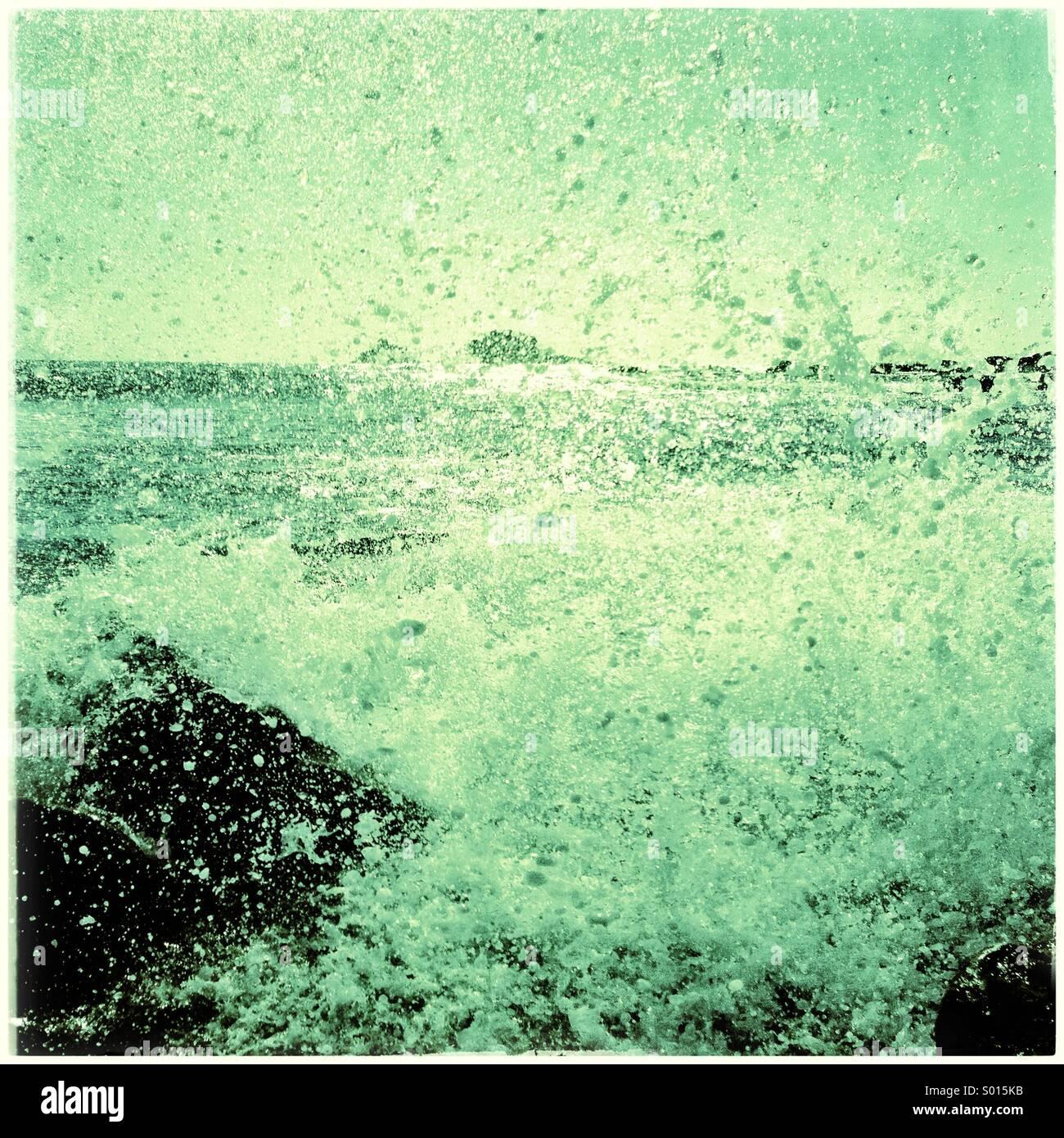 L'eau verte des vagues sur la plage des roches à Photo Stock