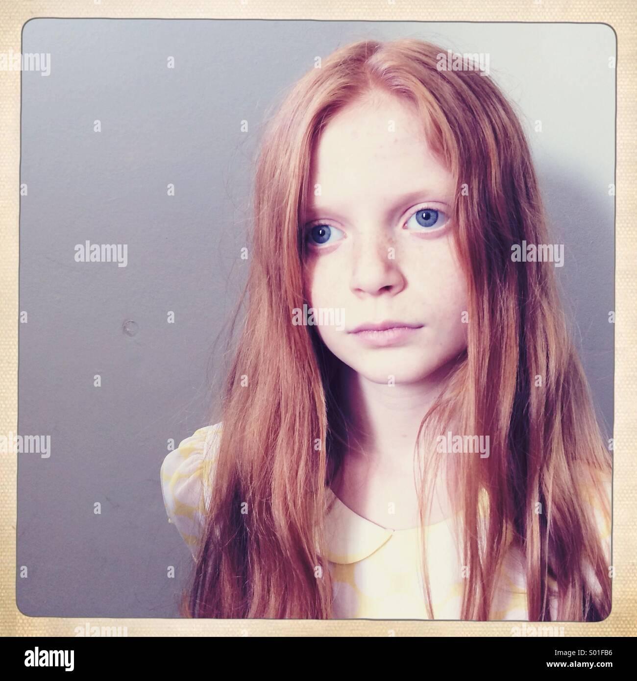 Fille aux cheveux rouge fixe et vide hors caméra avec un fond gris clair Photo Stock