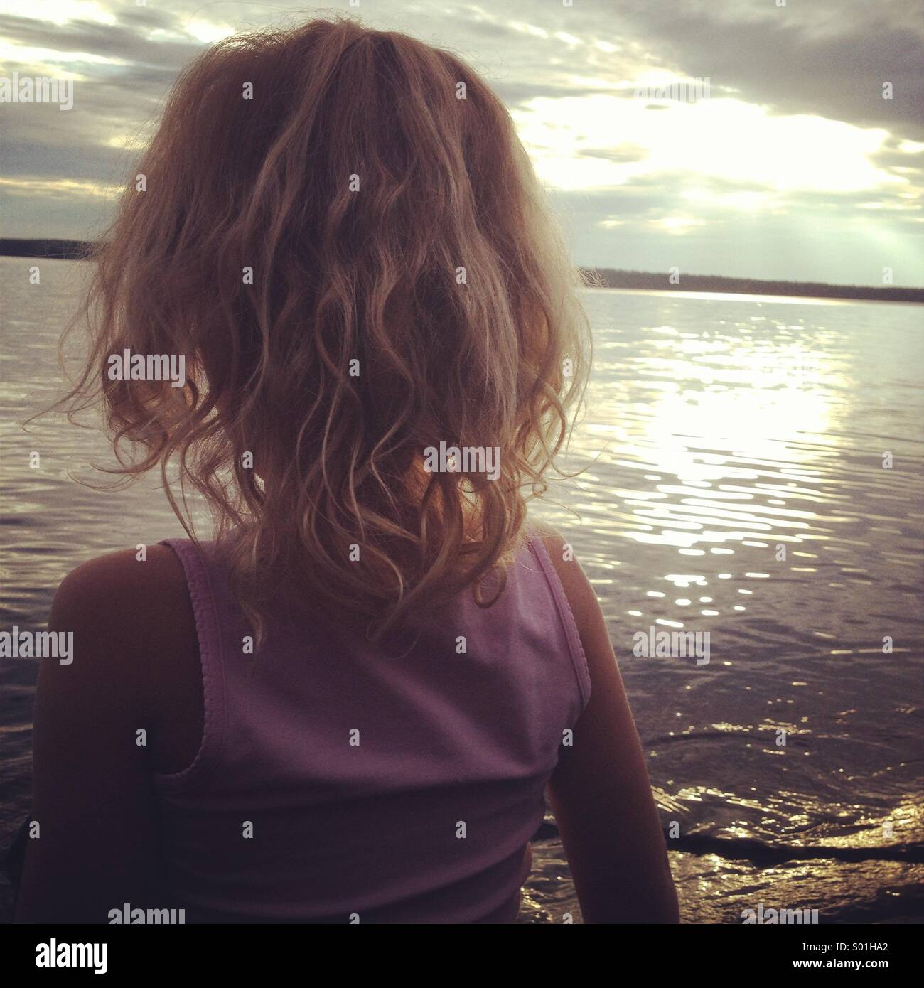Une fille blonde à regarder le coucher de soleil sur un lac orageux Photo Stock