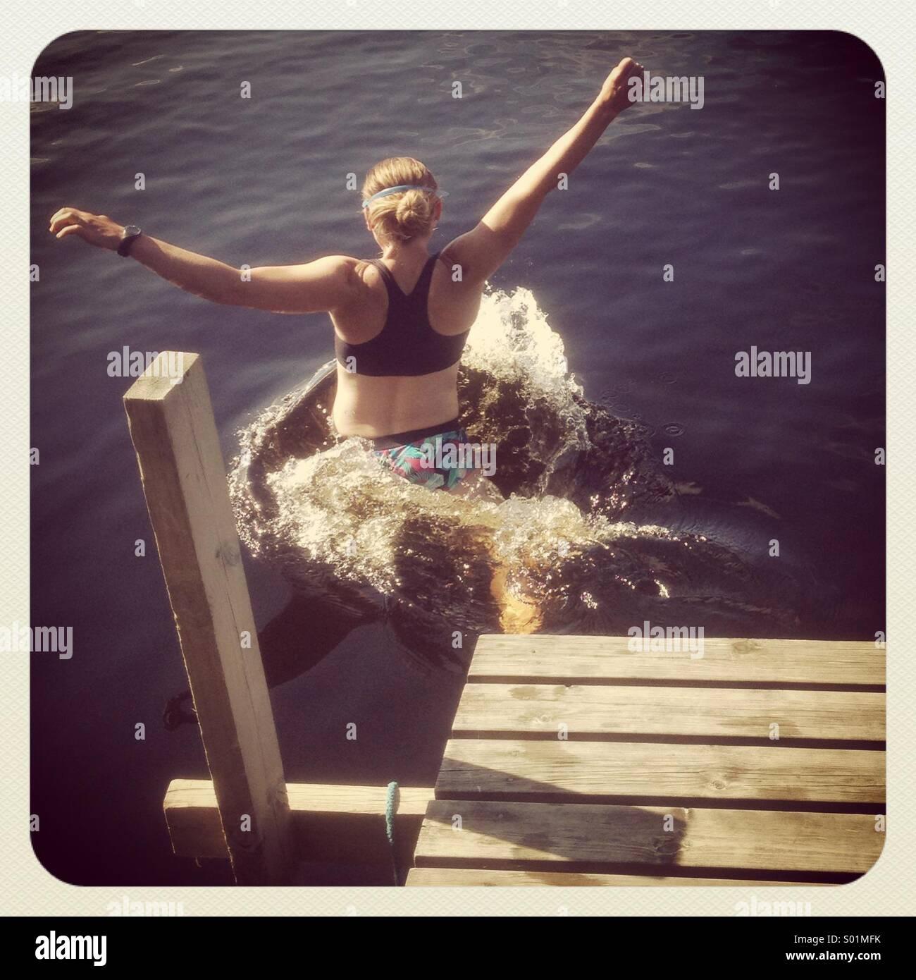 Une femme sautant hors d'une jetée dans un lac Banque D'Images