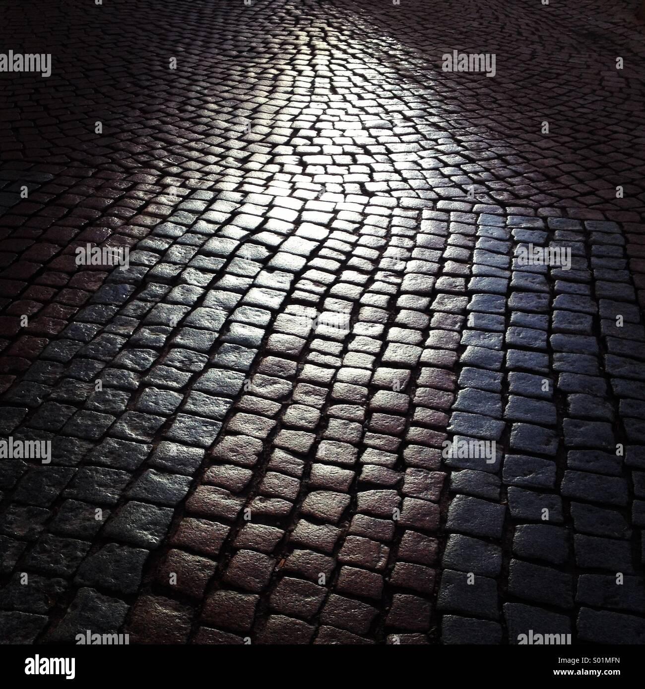 Une rue pavée humide brillant dans la lumière du soleil Photo Stock