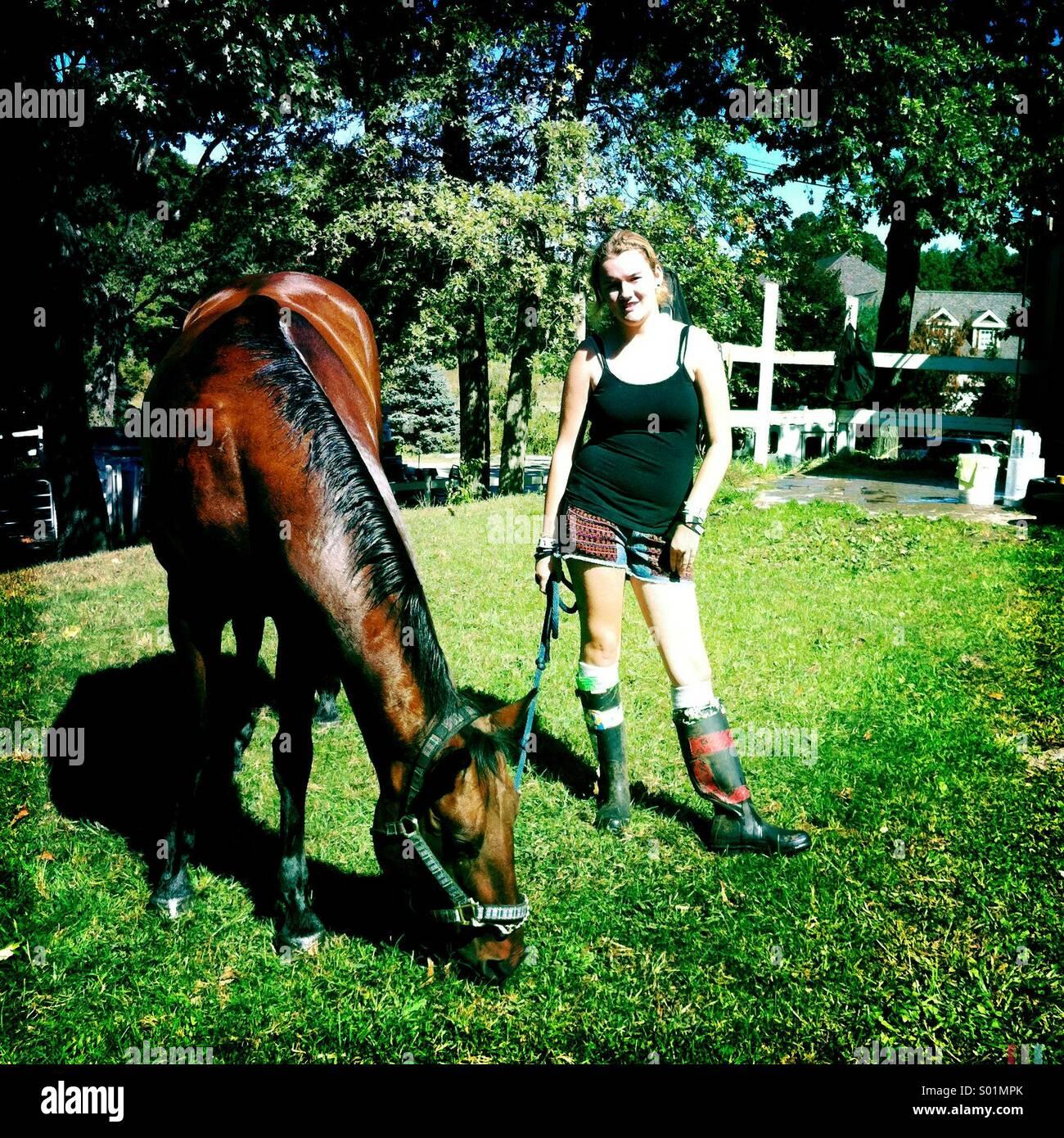 Adolescente avec son cheval mange de l'herbe Photo Stock