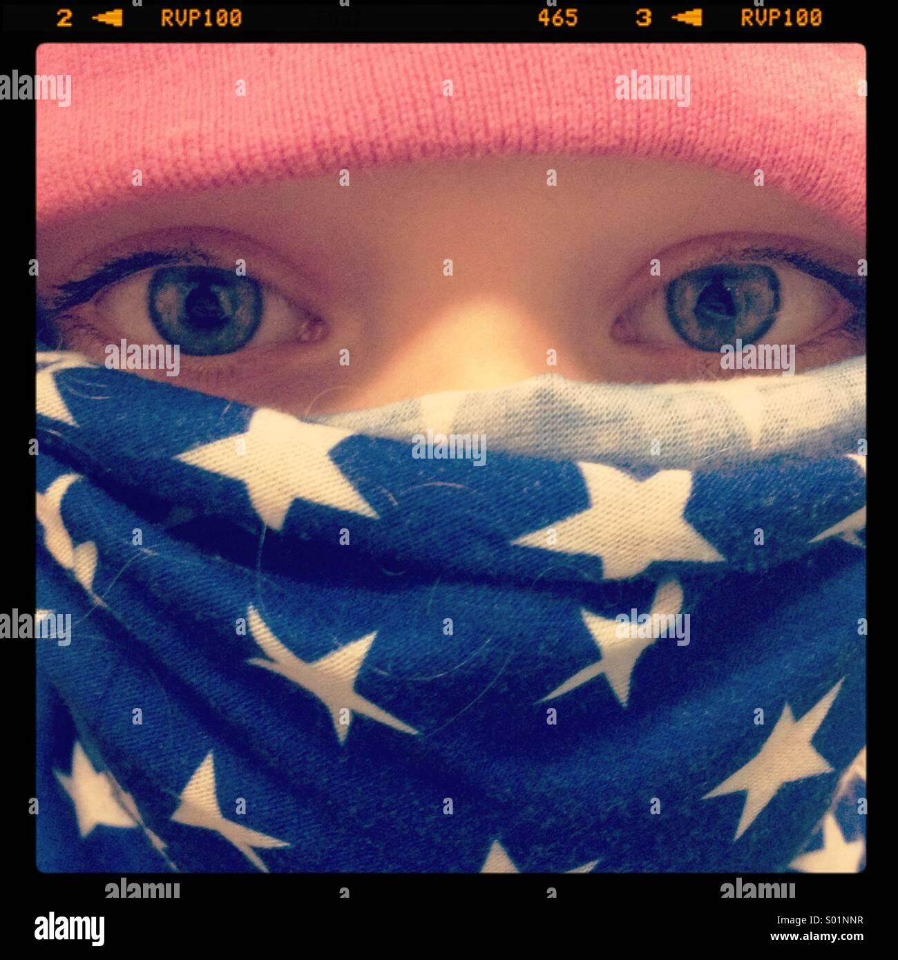 Un gros plan d'une petite fille protégée contre le froid avec un drapeau écharpe et chapeau rose Photo Stock