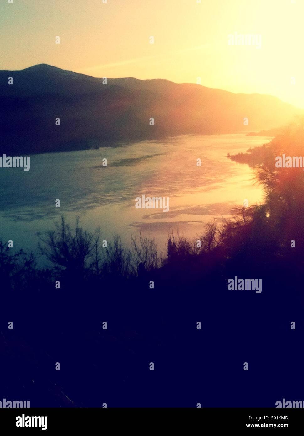 Coucher du soleil dans la vallée avec rivière entre les pentes Photo Stock