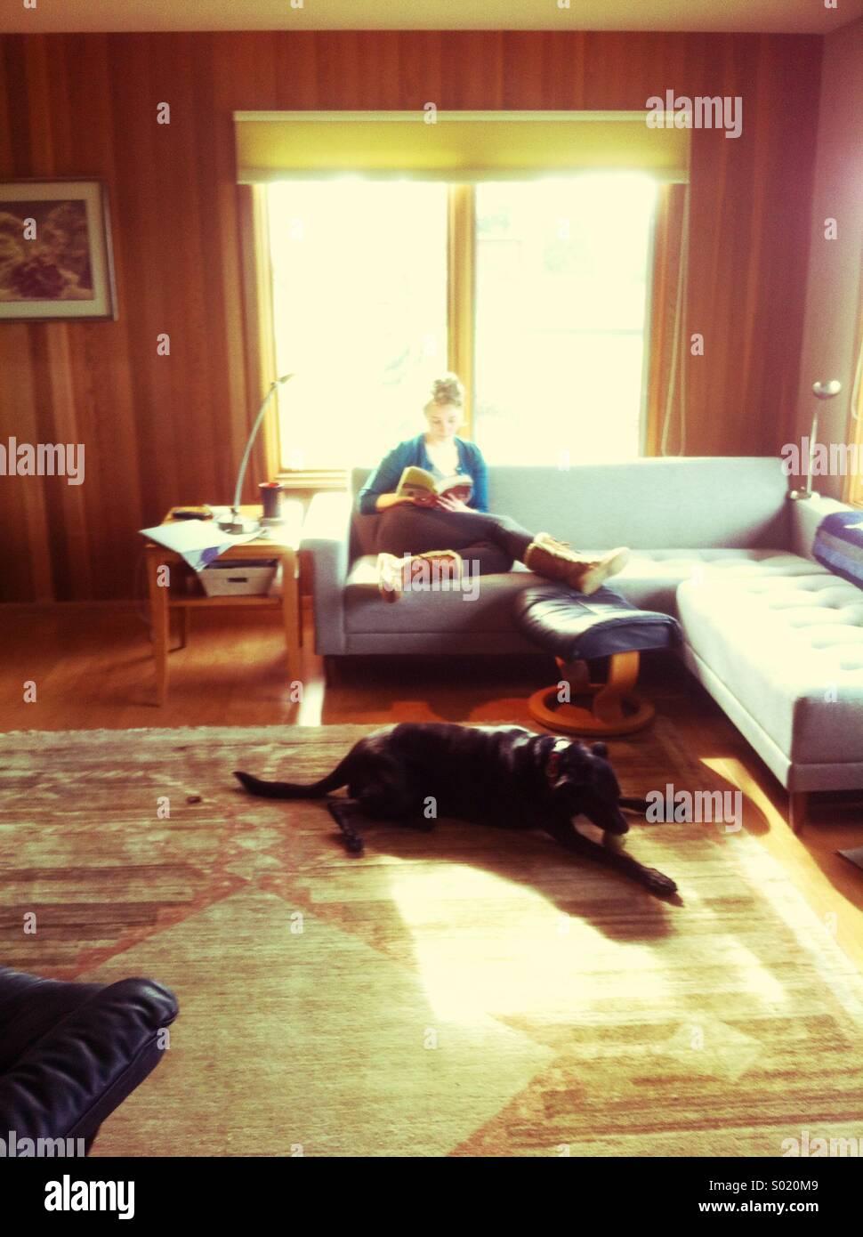 Jeune femme lisant dans la salle de séjour avec chien noir sur un tapis Photo Stock