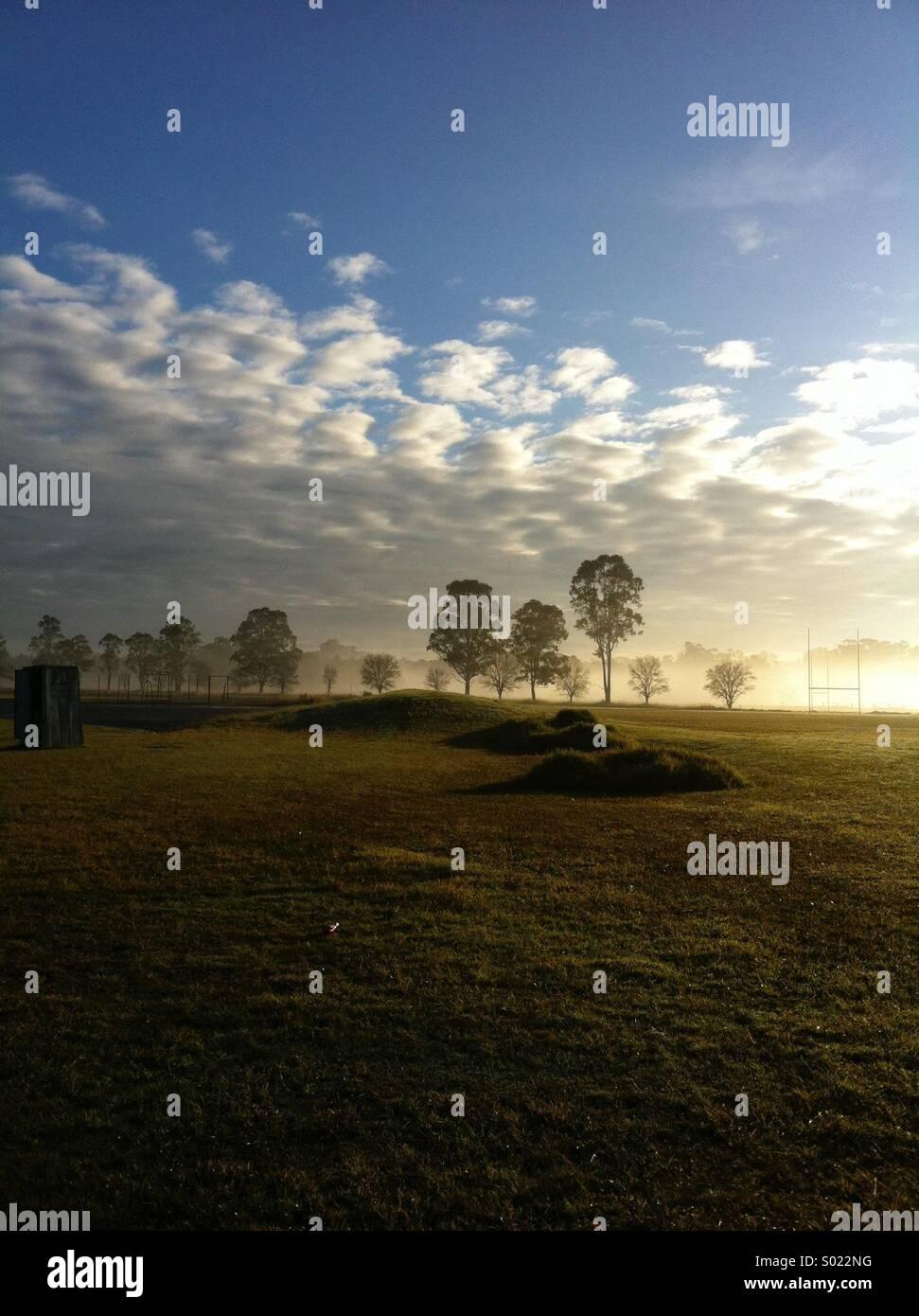 Scène rurale tôt le matin avec ciel nuageux et poteaux de rugby Photo Stock