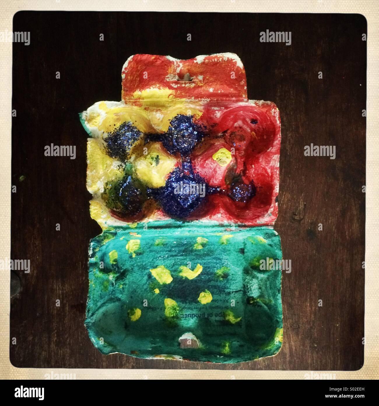 Boîte d'oeufs colorés peints et saupoudré de paillettes par un enfant Photo Stock