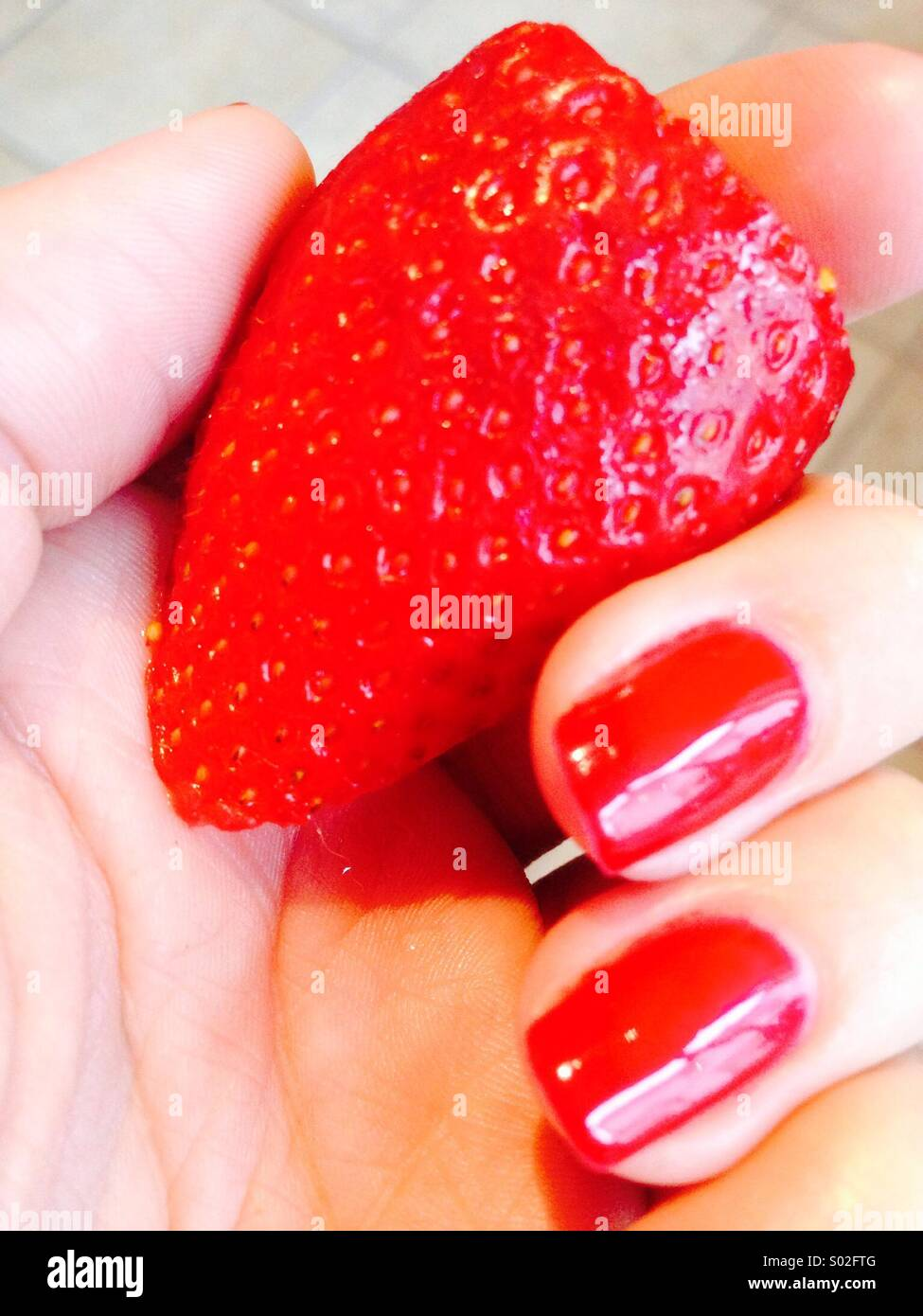 Strawberry a tenu à la main avec des ongles peints en rouge Photo Stock