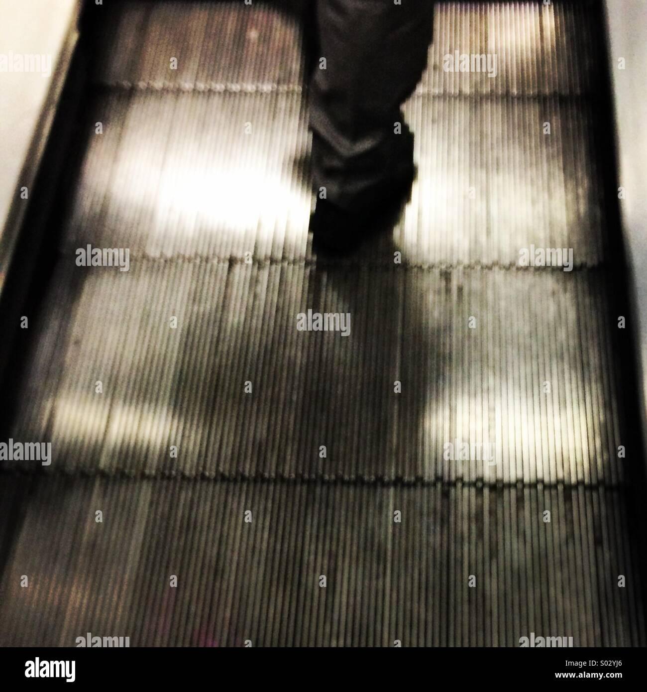 Jambes floues marche sur un tapis roulant escalator. Photo Stock