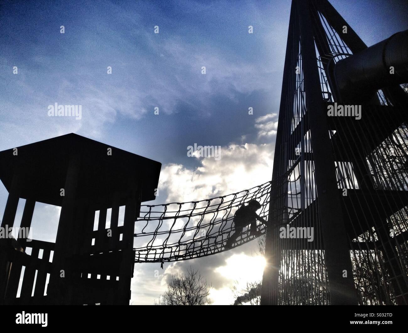Un jeune garçon grimpe entre deux structures dans un parc de jeu. Photo Stock