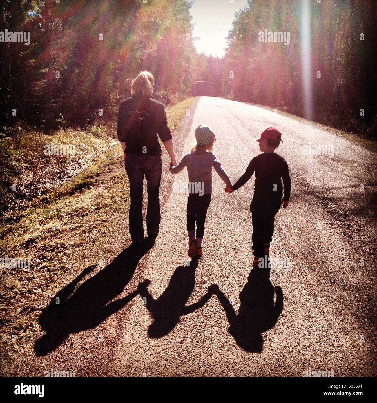 Une mère marche main dans la main avec ses enfants dans le soleil du printemps... Banque D'Images