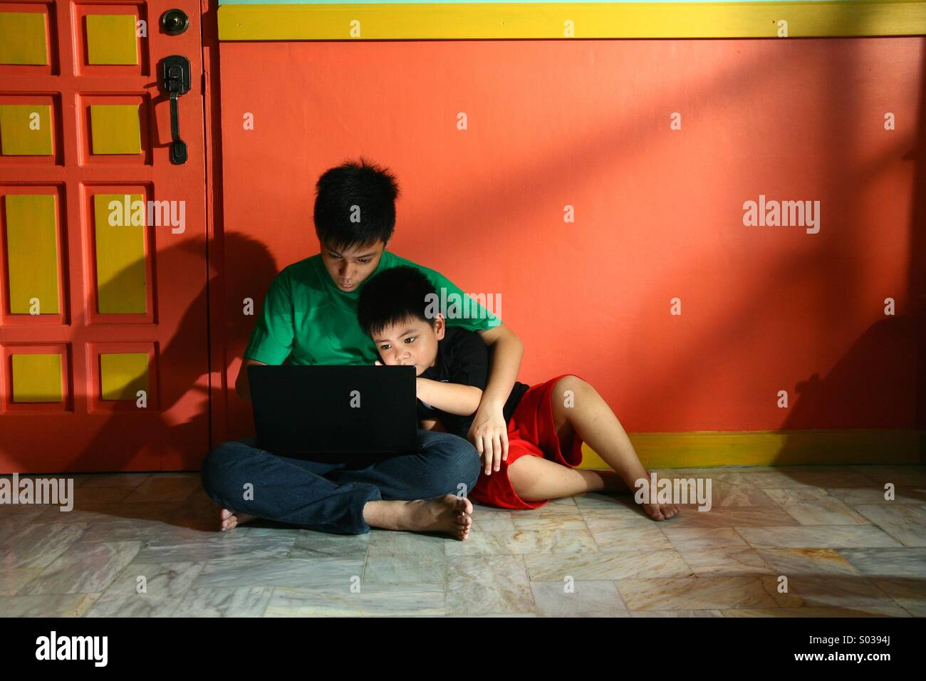 Les jeunes enfants d'Asie, ou de frères et sœurs, avec un ordinateur portable dans un salon vide Photo Stock