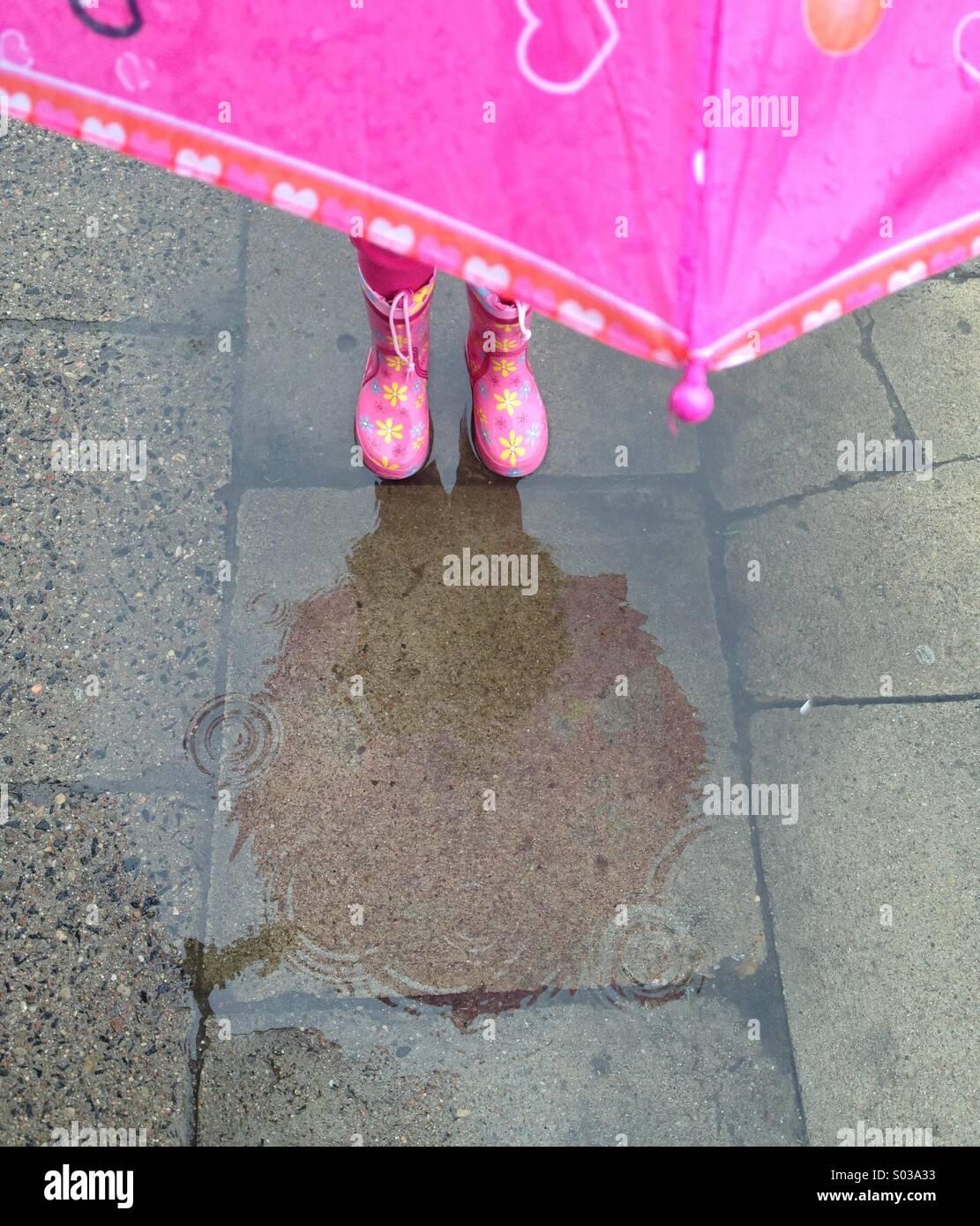 En rose enfant debout dans la flaque gumboots Photo Stock