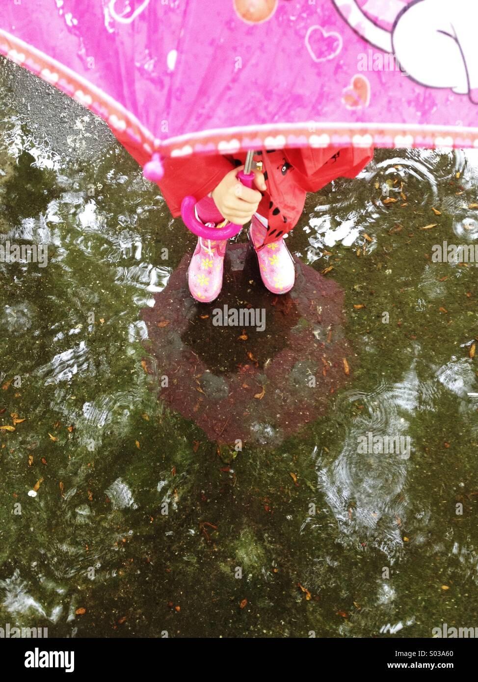 Avec parapluie enfant debout dans la flaque Photo Stock