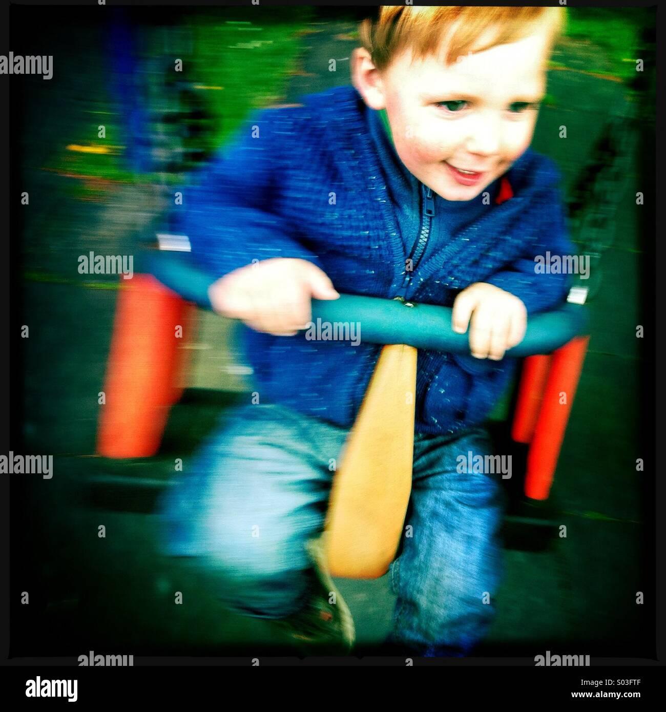 Un jeune garçon s'amusant sur une balançoire à l'jouer park Photo Stock