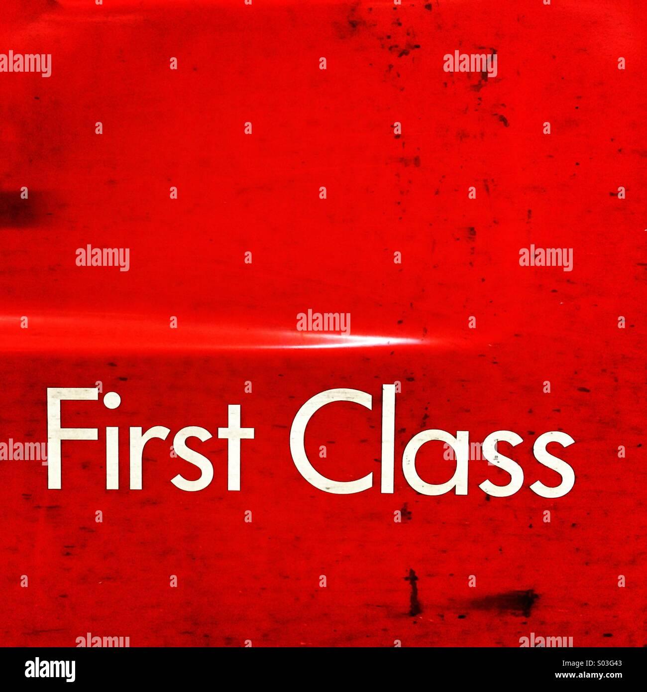 Première Classe enseigne sur un train rouge sale porte. Photo Stock