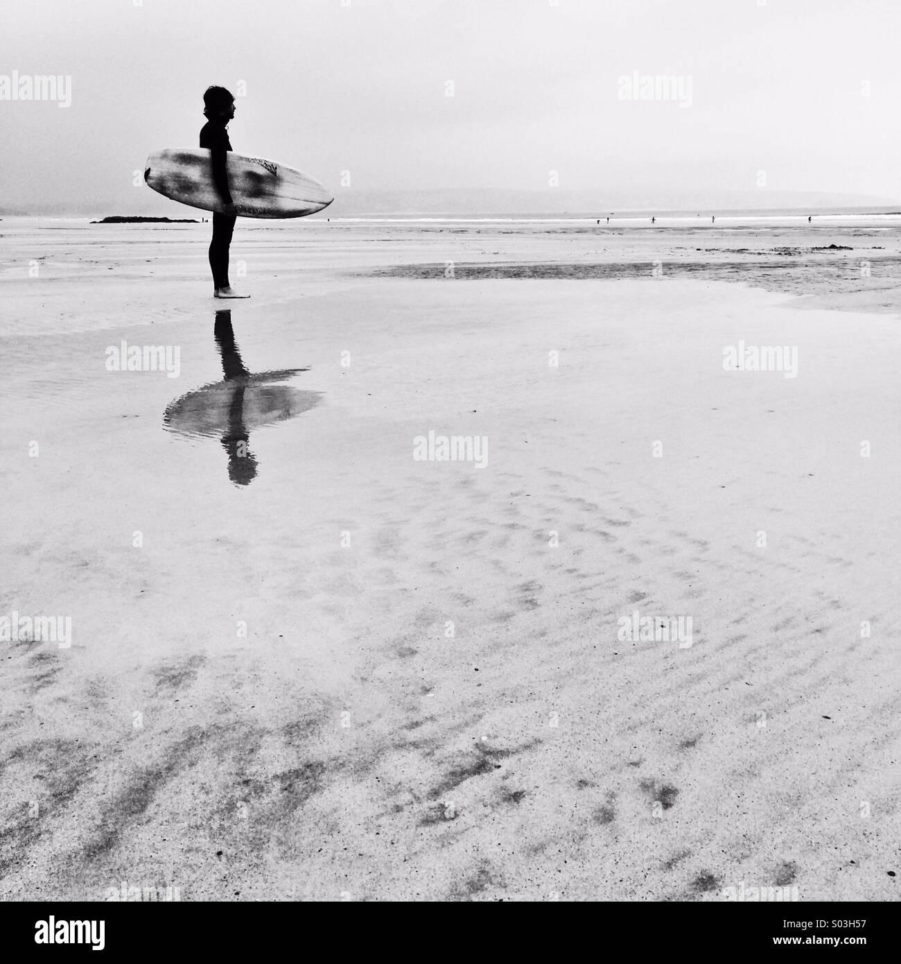 Contrôle du surfeur vagues en hiver à la première lumière. Photo Stock