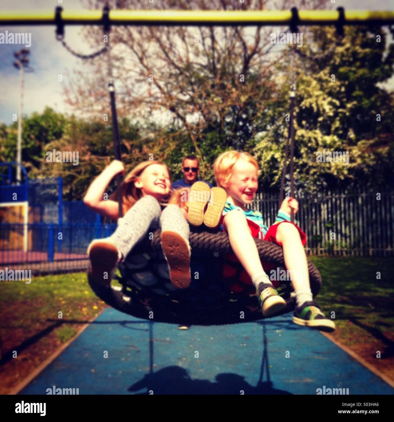 Les enfants sur une balançoire Photo Stock