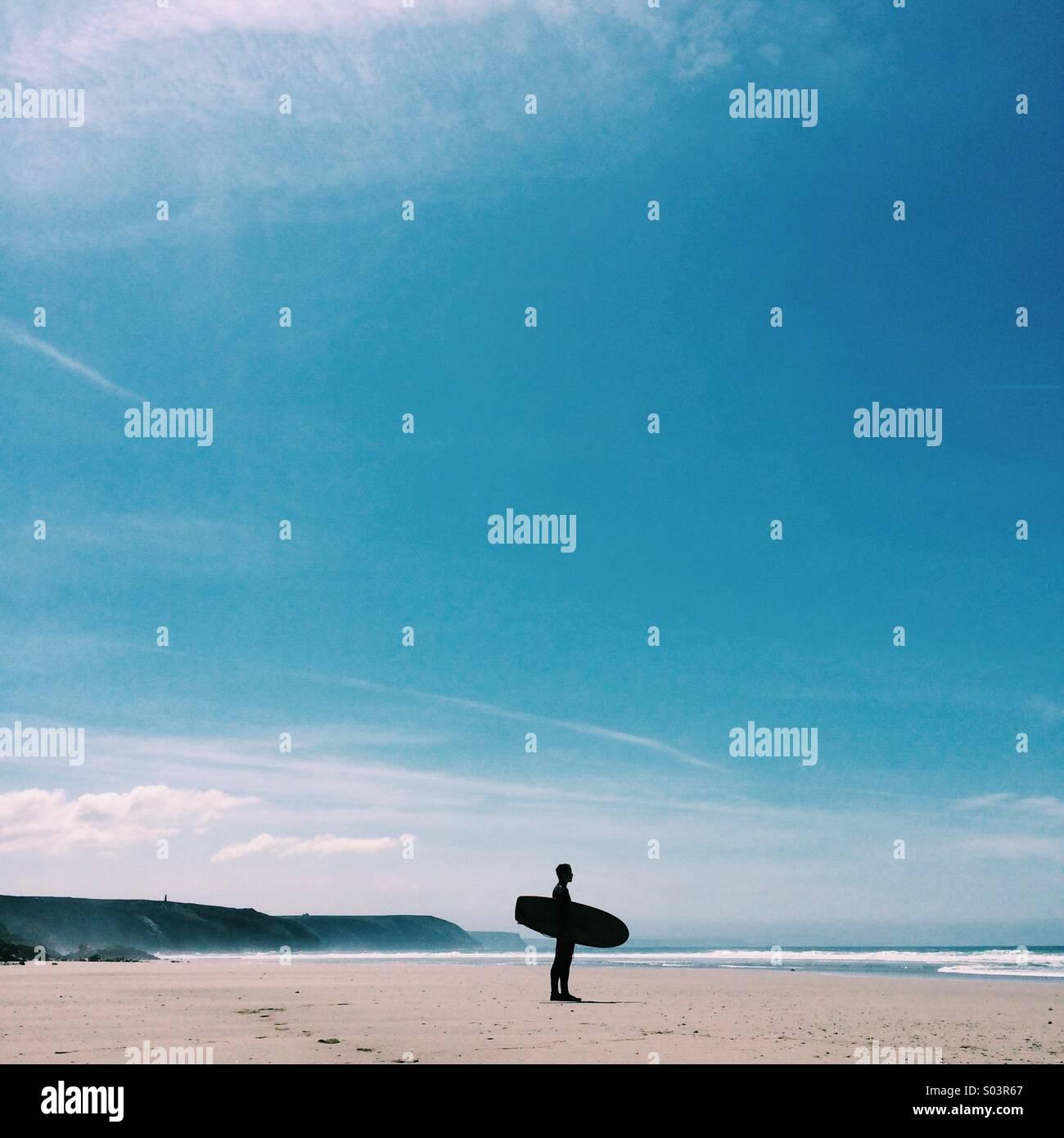 Vérification du surfer les vagues, avec un ciel bleu clair en été. Photo Stock