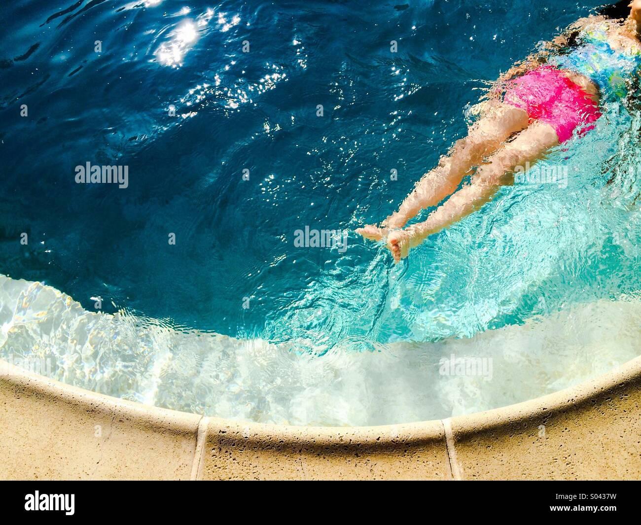 Jeune fille flottant sur son dos dans une piscine Photo Stock