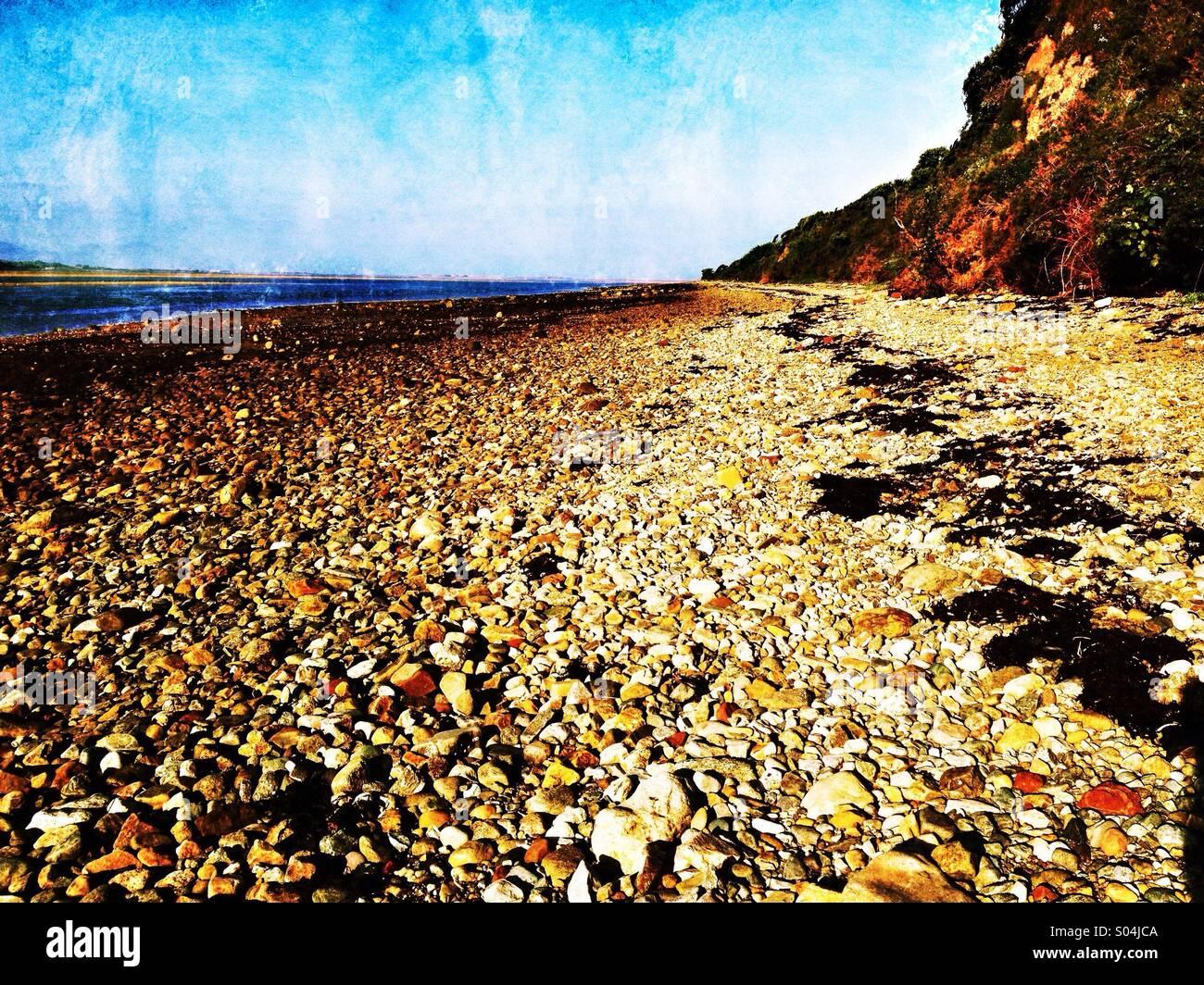 Plage de galets par le détroit de Menai sur Anglesey Photo Stock
