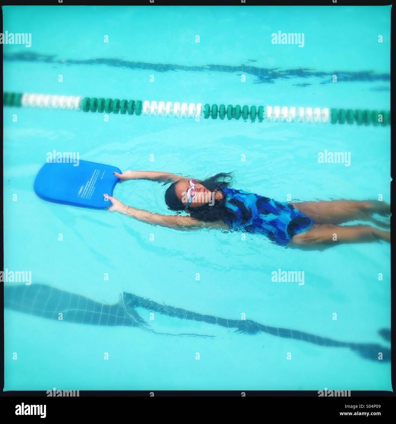 Petite fille d'apprendre à flotter sur son dos Photo Stock