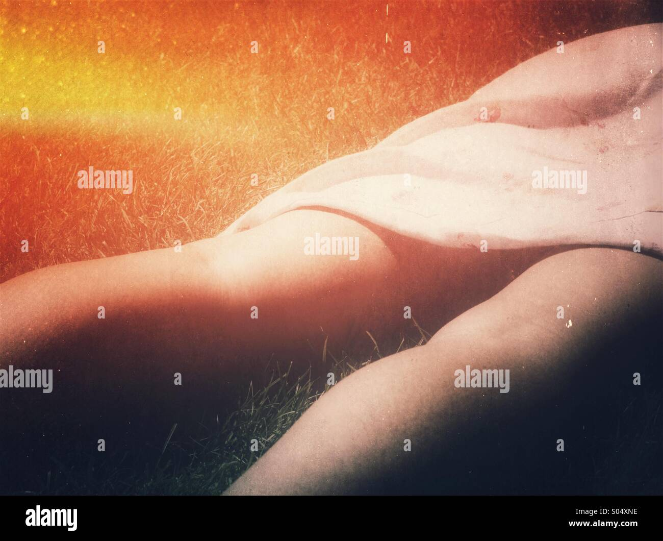 Concept de soleil. Les jambes et la jupe d'une femme en train de bronzer sur l'herbe Photo Stock