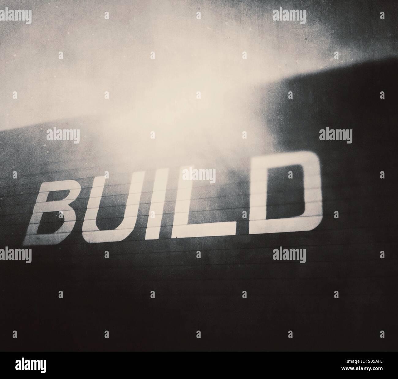 Le mot 'build' sur le côté du bâtiment de bois. Photo Stock