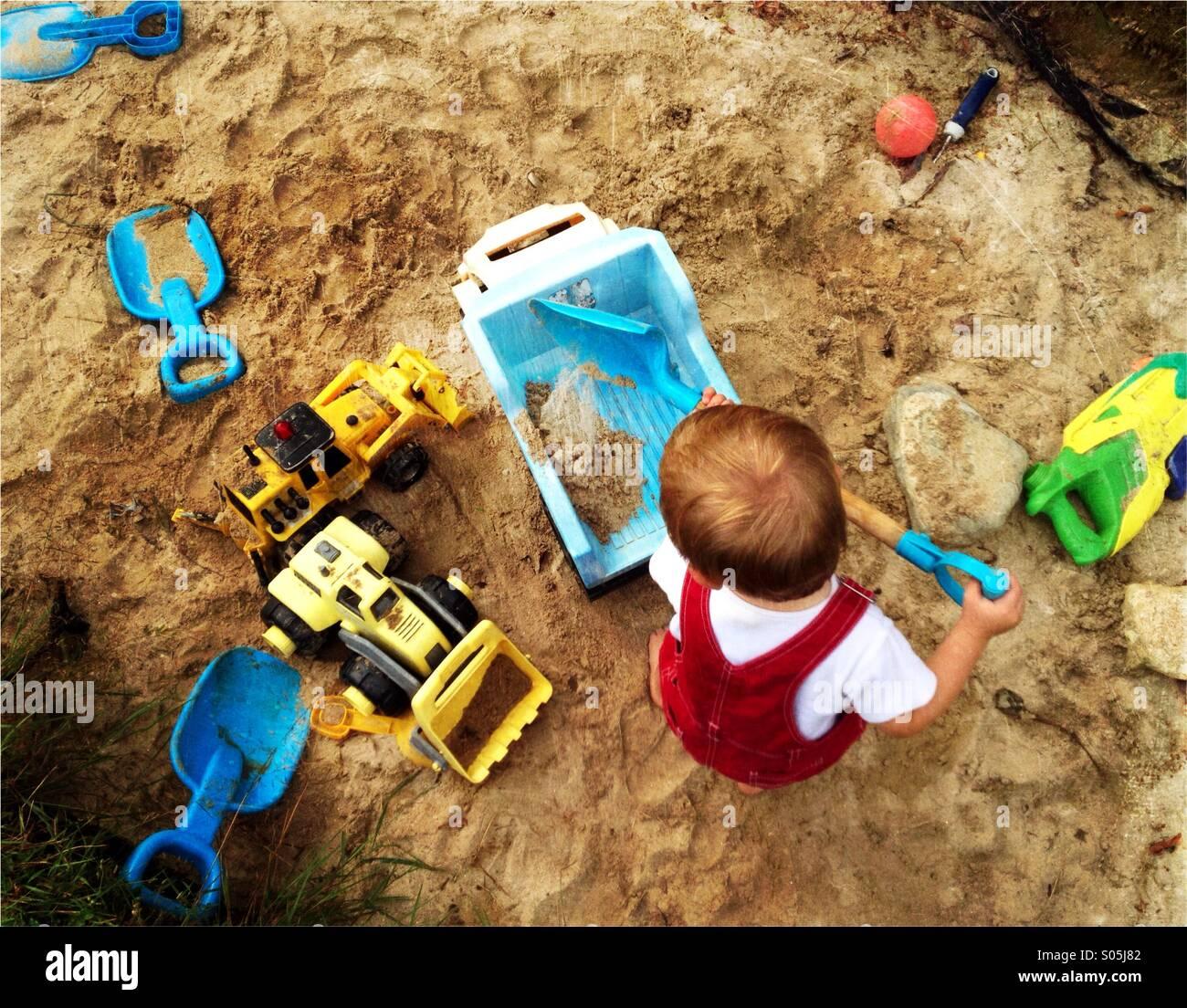 Bébé garçon joue avec une pelle et camions dans un grand bac à sable. Photo Stock