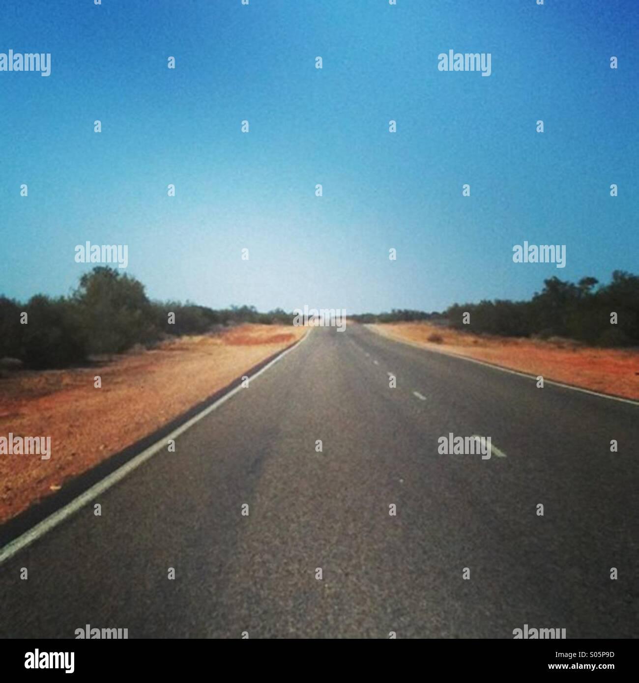 Et longue route droite dans l'ouest de l'outback australien Photo Stock