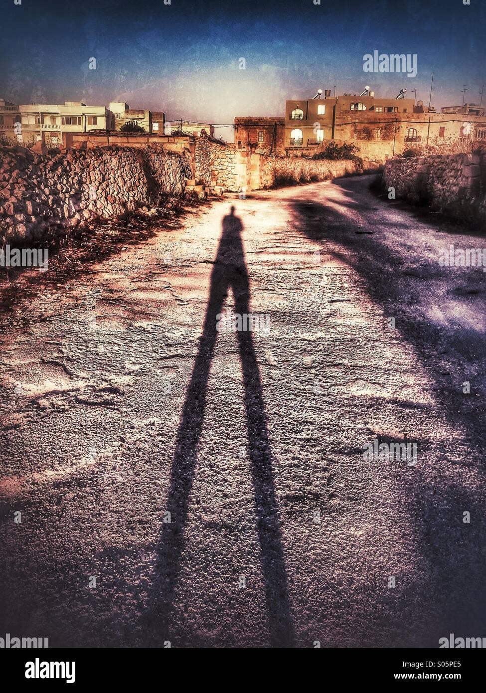 Ombre d'homme qui s'étend jusqu'à l'aube d'une route de campagne Photo Stock