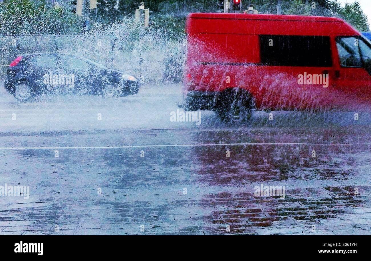 Une fourgonnette et une voiture roulant dans la pluie Photo Stock