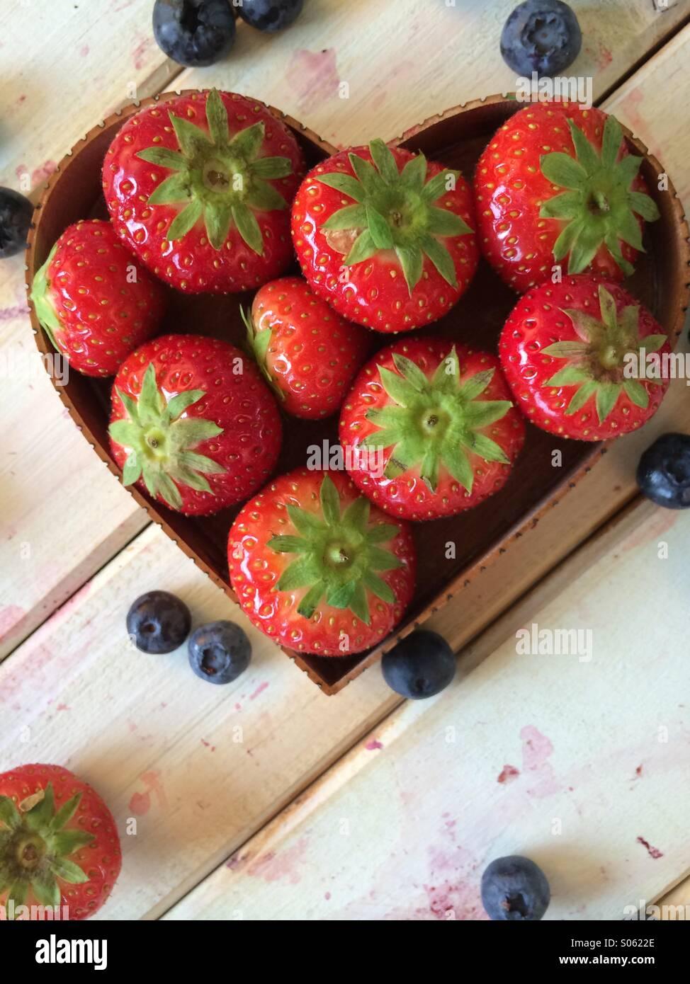 Fraises fraîches dans l'amour coeur panier de forme et les bleuets sur tableau dans le style rétro Photo Stock