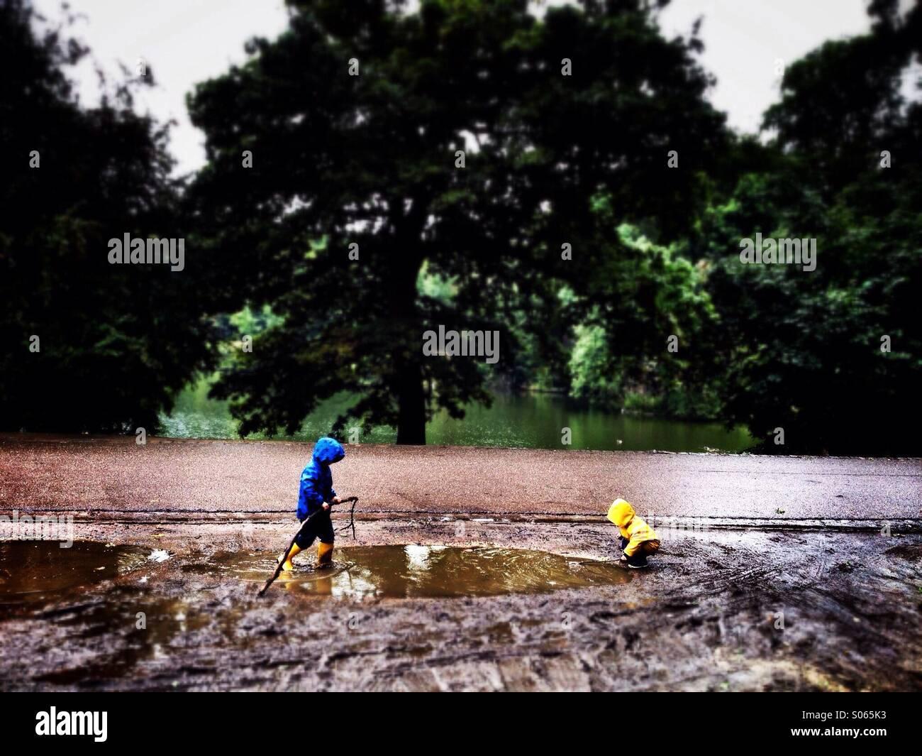 Vaststaand les enfants jouant dans une flaque. Photo Stock