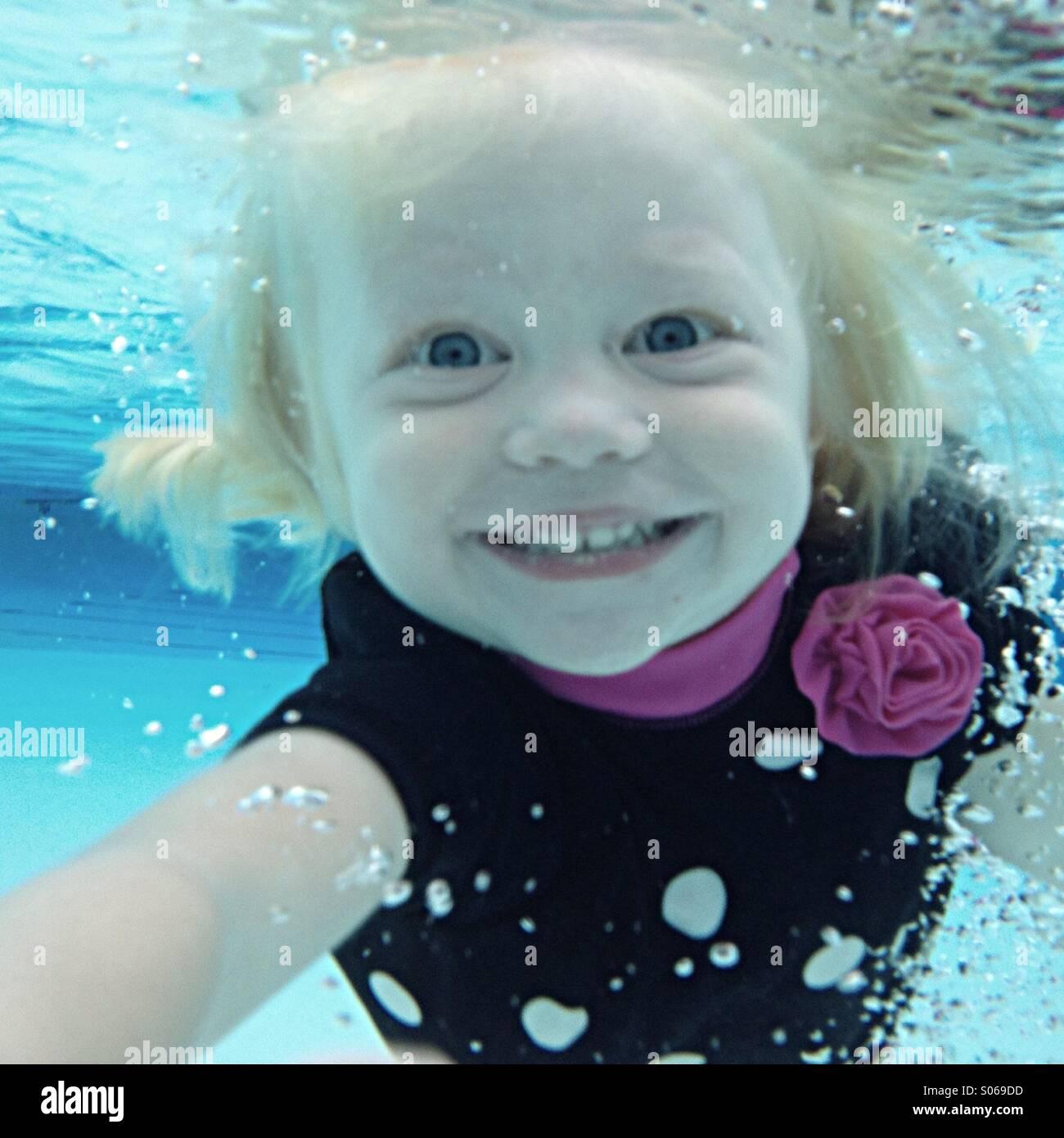 Jeune fille sourire comme elle nage vers la caméra sous l'eau. Photo Stock