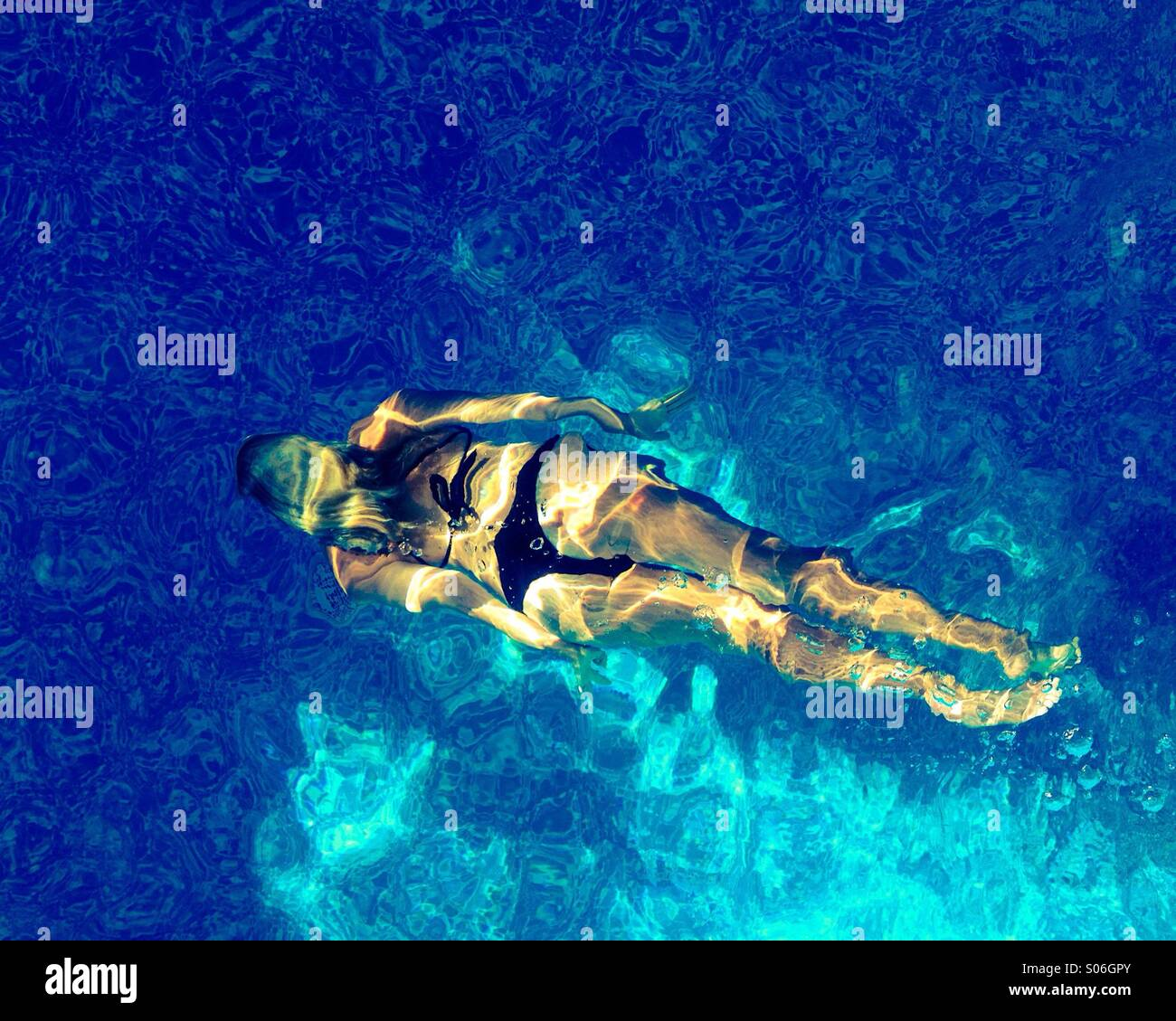Blonde aux cheveux longs, woman in bikini nager sous l'eau dans les eaux chaudes de nettoyage d'une piscine Photo Stock