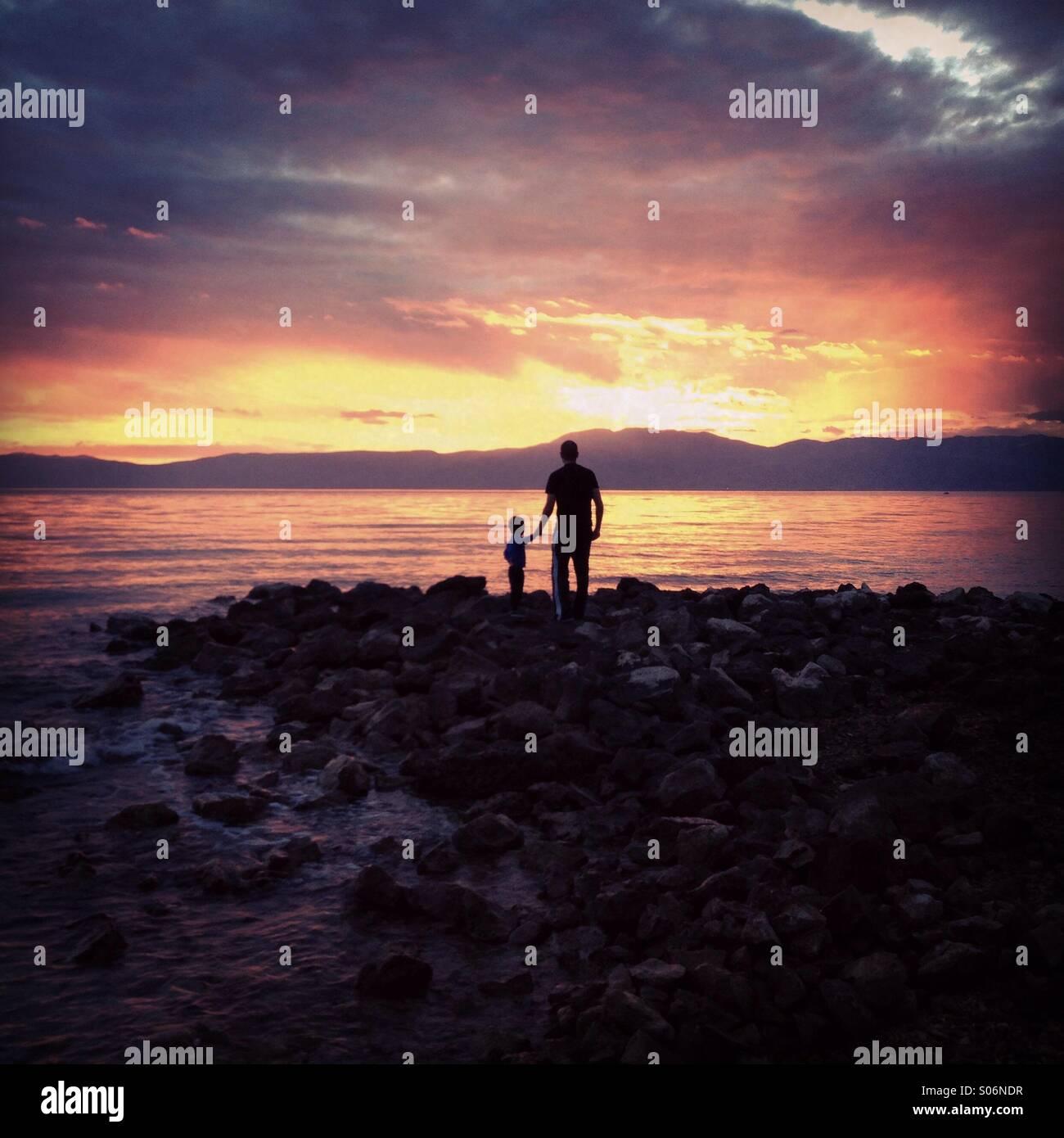 Le père et le fils par la mer au coucher du soleil Photo Stock