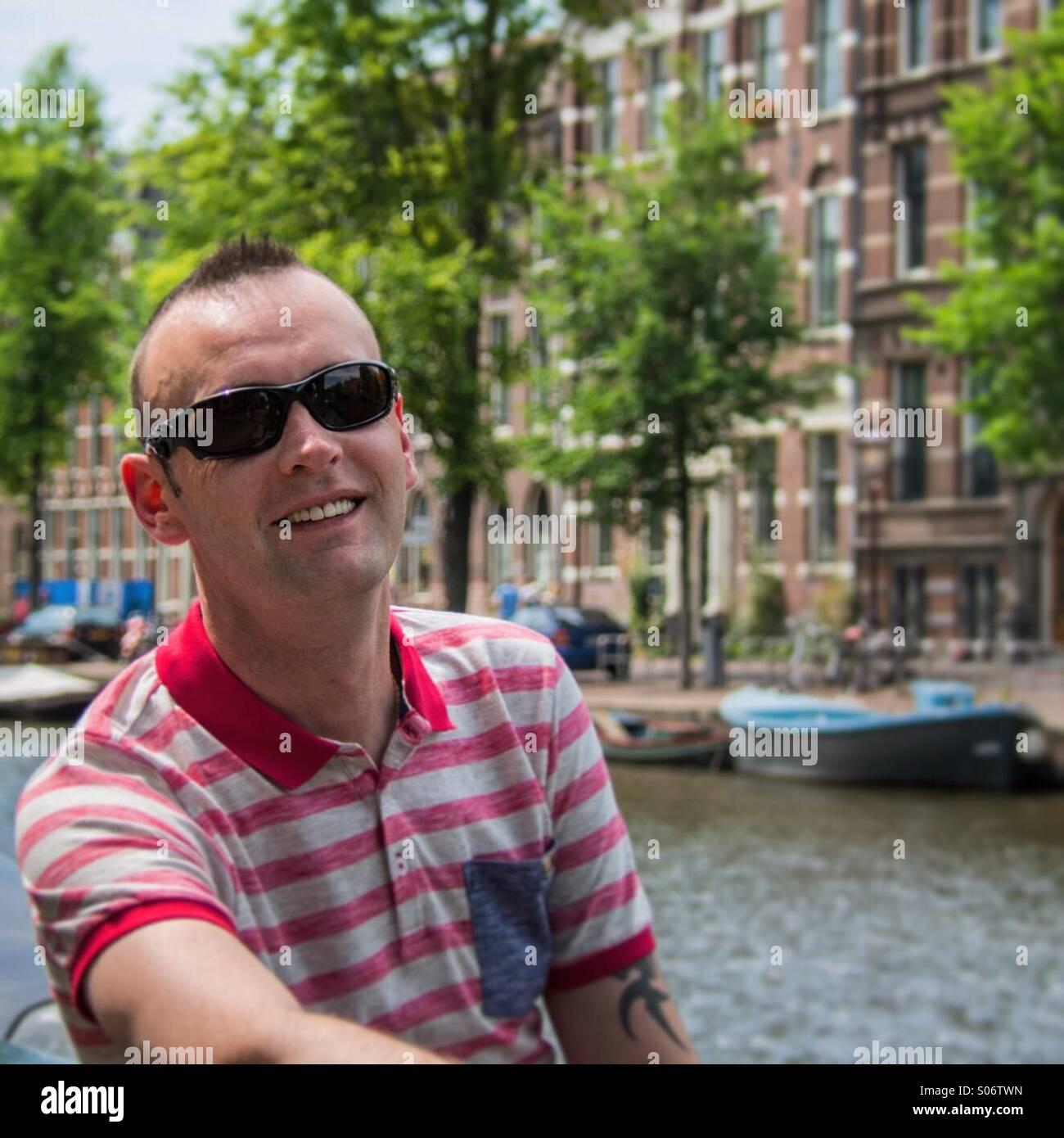 Homme assis par canal à Amsterdam Photo Stock