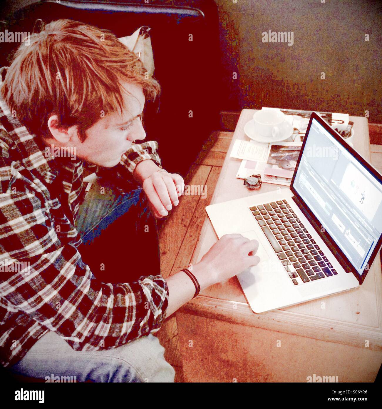 Un jeune homme travaillant sur un ordinateur portable Photo Stock