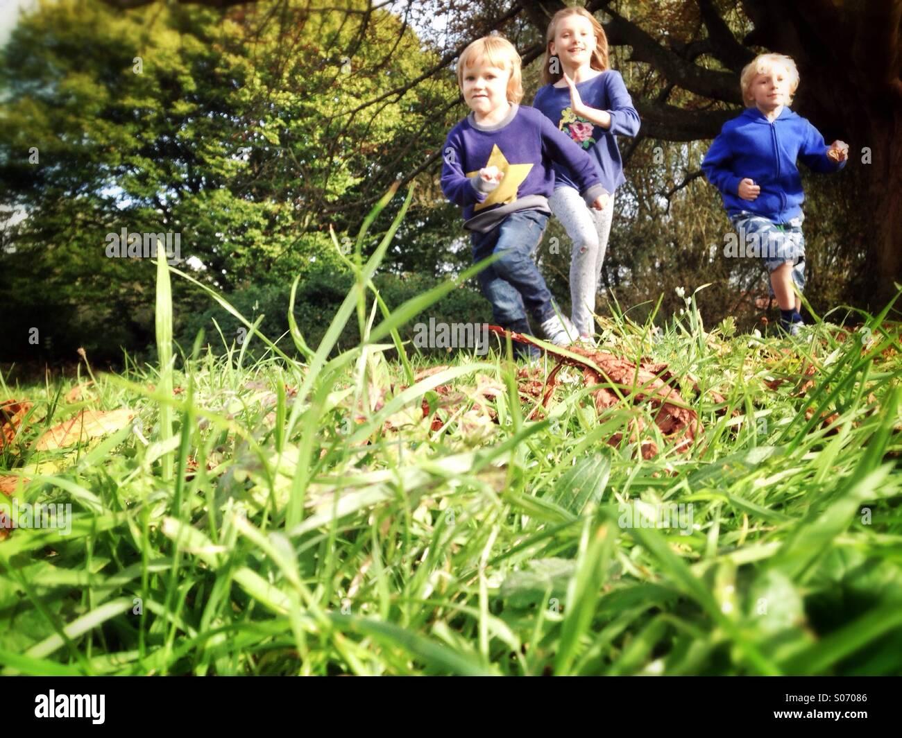 Les enfants courent à travers un champ Photo Stock