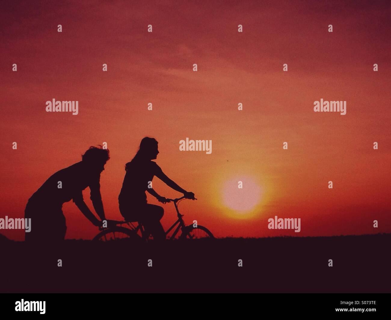 Couple aimant sur le vélo pendant le coucher du soleil Photo Stock